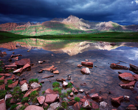 Afternoon sunlight on the Maroon Bells fourteeners with dark thunderclouds above as seen reflected in a pond in the Elk Mountains of Colorado in July.