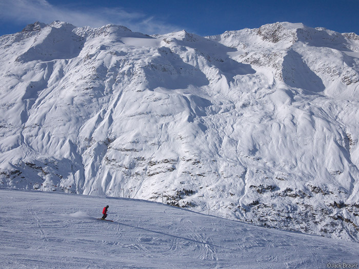 A skier at Obergurgl dwarfed by enormous snow smothered mountains.