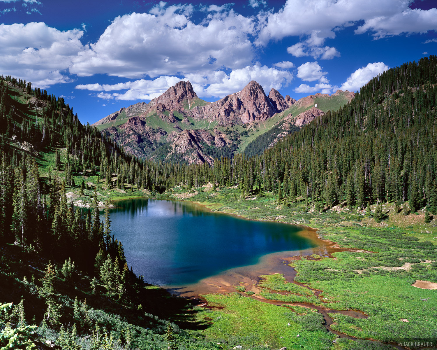Pigeon and Turret Peaks, of the Needle Mountains, tower above this remote alpine lake in the San Juan Mountains - July