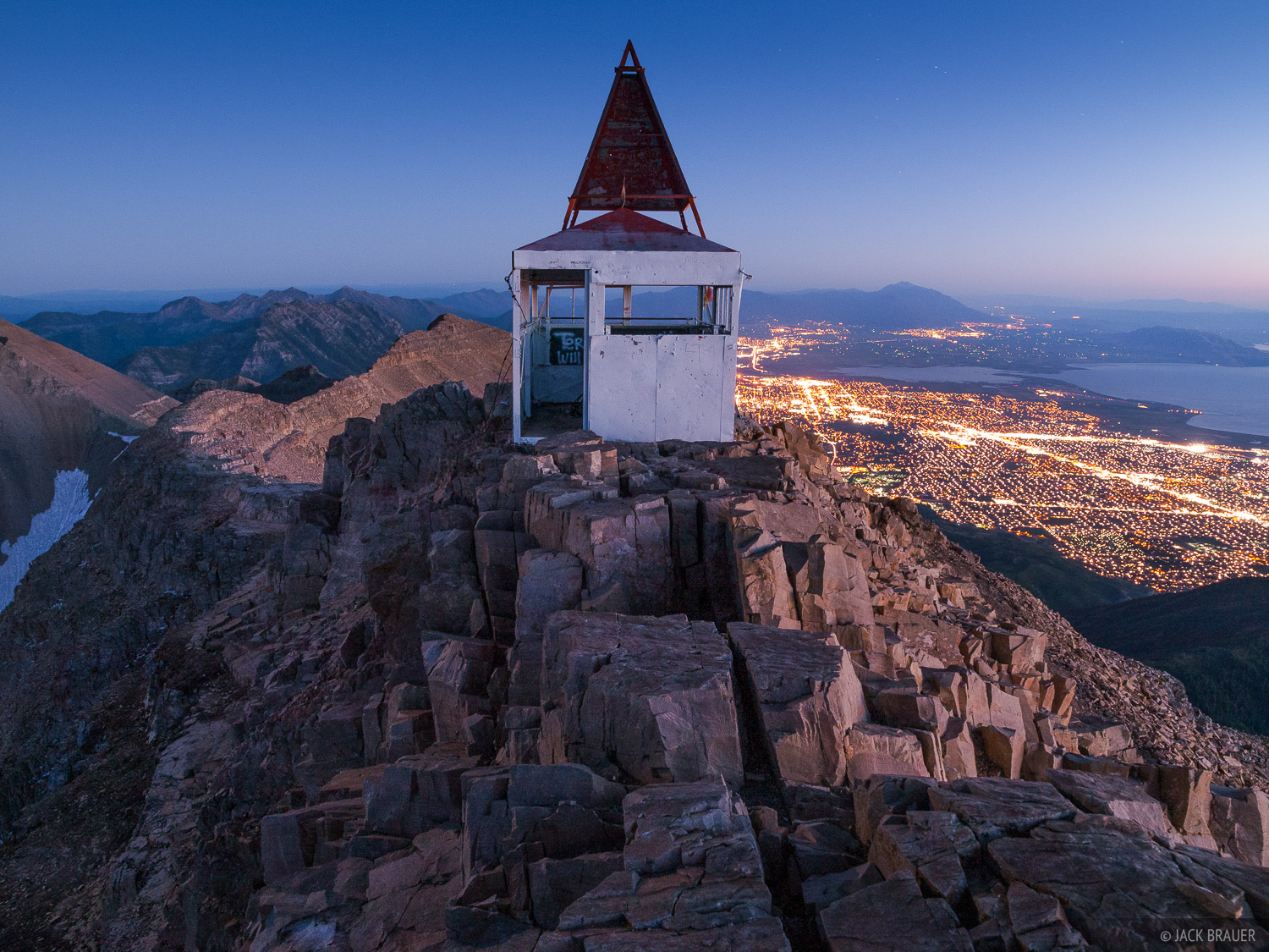 The summit shelter on Mount Timpanogos, with the city lights of Provo, Utah far below.