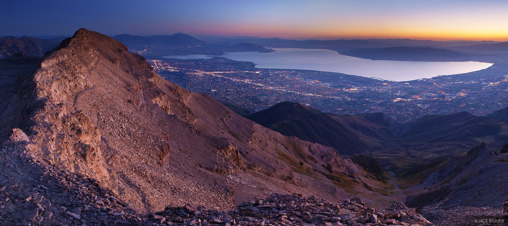 Dusk panorama of Utah Lake and the city lights Provo, Utah, as seen from near the summit of Mount Timpanogos, 7,000 feet higher...
