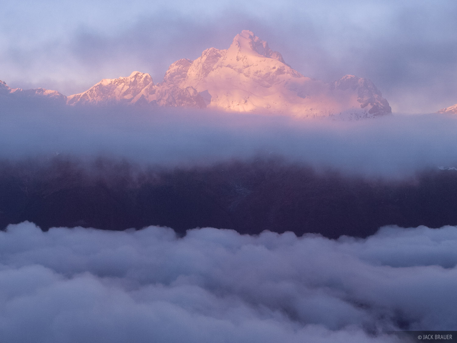 Sunrise light shines on Mt. Gifford in the Darren Mountains, as a sea of clouds breaks up.
