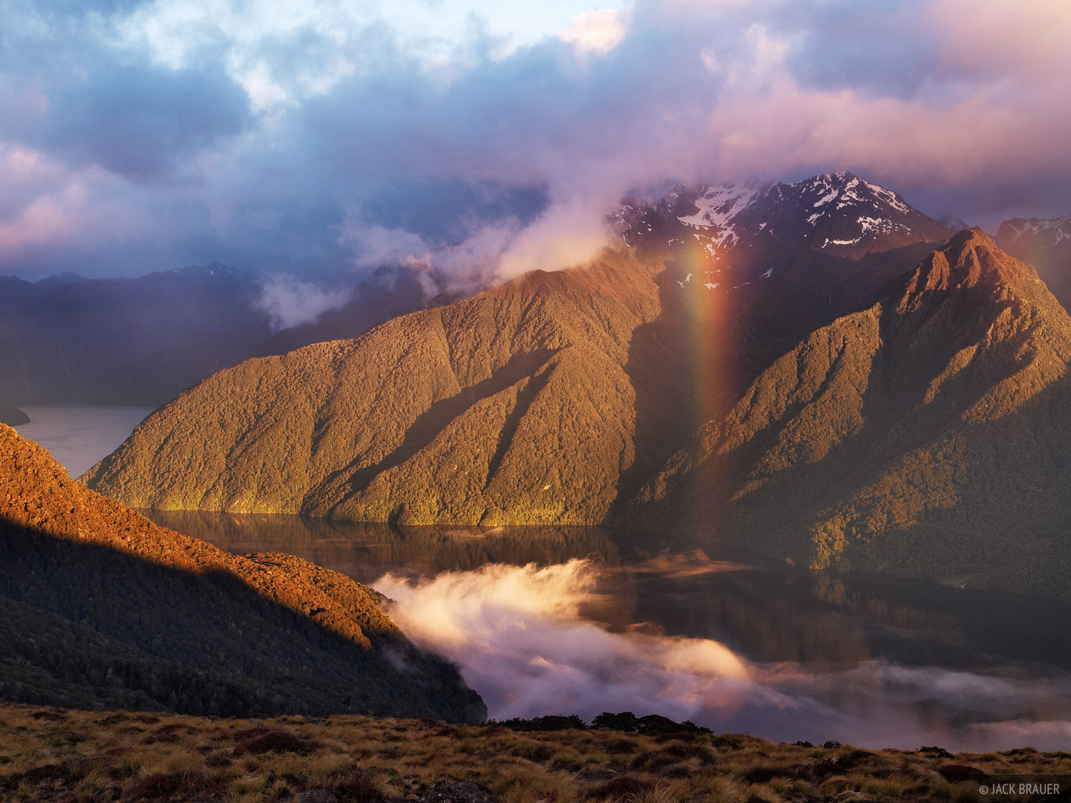 Sunrise rainbow over a fiord arm of Lake Te Anau, with the Murchison Mountains behind, as seen from the Kepler Track.