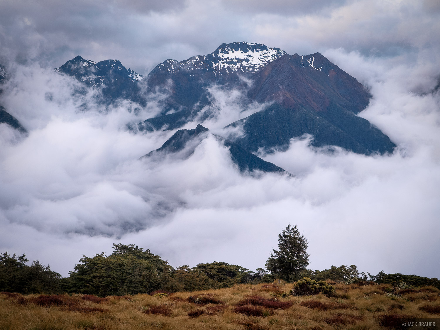The Murchison Mountains emerge from the clouds during stormy weather, as seen from near the Luxmore Hut along the Kepler Track...