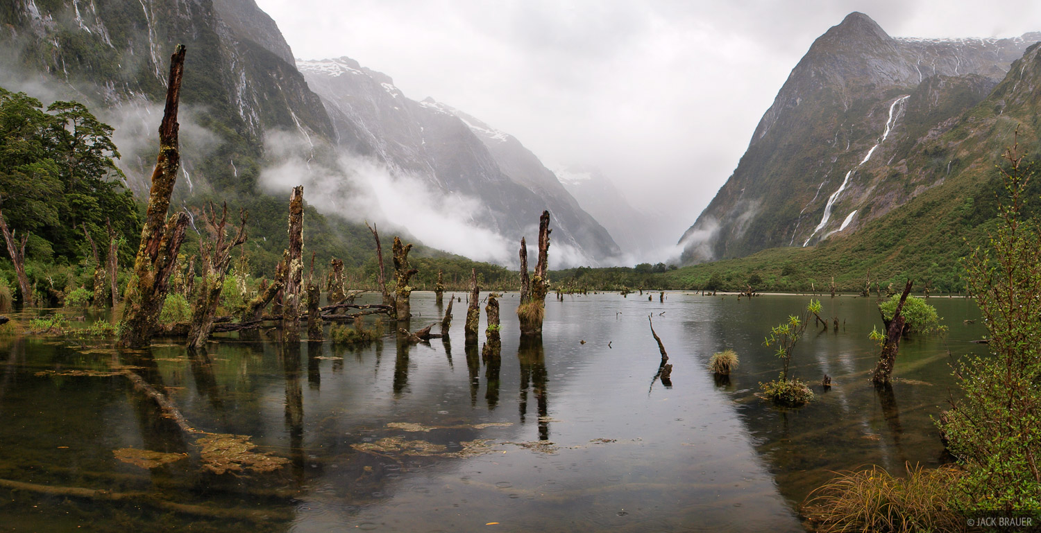 Waterfalls pour off the sheer vertical walls of the Fiordland mountains during a wet, rainy day along the Clinton River on the...