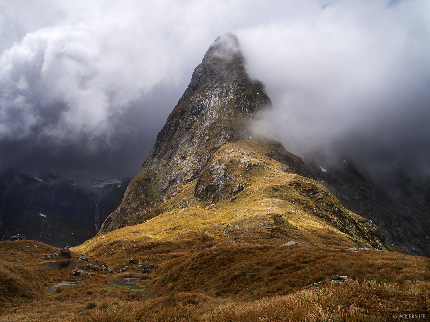 The jagged peak of Mt. Balloon cuts through the clouds on Mackinnon Pass, the high point of the Milford Track, New Zealand's...