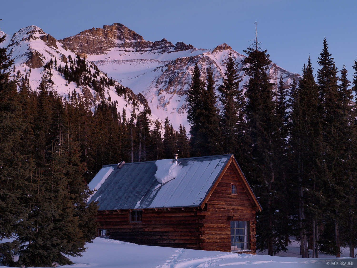 Vermilion Peak, 13,894 ft., towers over the backcountry cabin.