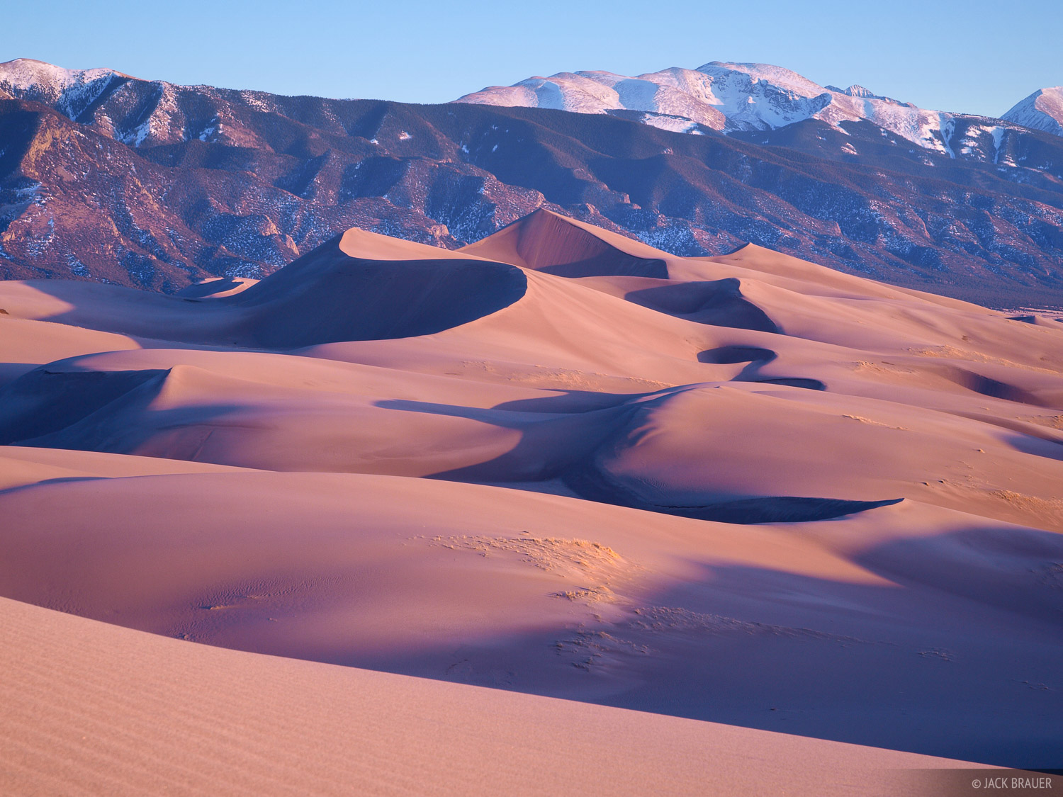 Warm sunset light shines on Star Dune, the tallest dune in the national park. Star Dune rises 750 feet above the San Luis...