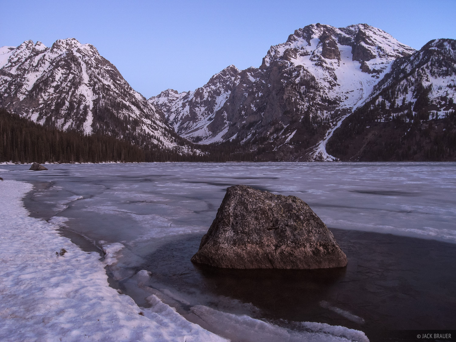 Dawn light on the shores of partially frozen Leigh Lake, looking towards the rugged peaks of Leigh Canyon.