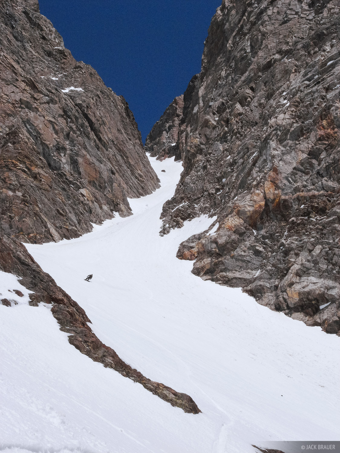 Looking up at the Southwest Couloir on Mt. Moran, as Jason King snowboards down.