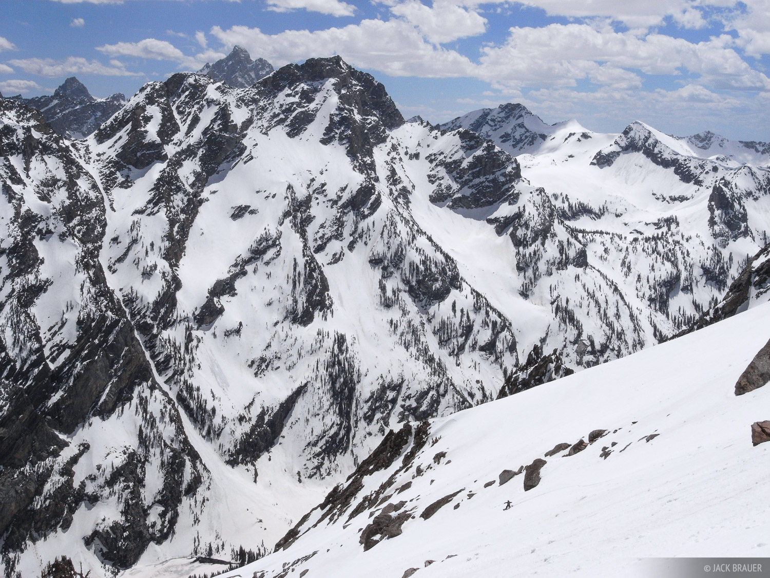 Darrell Miller snowboards down the long southern slopes of Mt. Moran, with a rugged Teton backdrop.