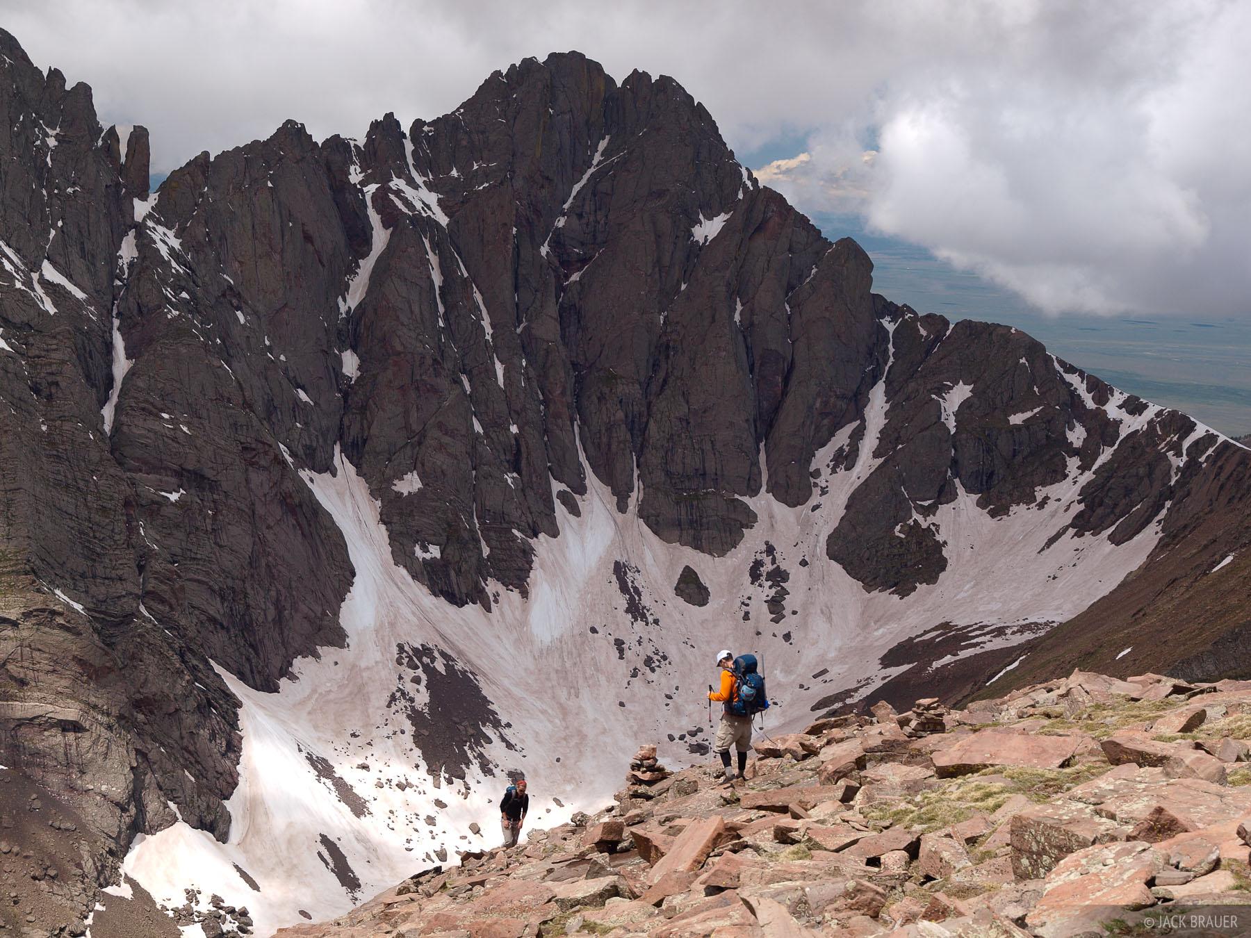 Hikers on the slopes of Humboldt Peak, with Crestone Peak towering behind - June.