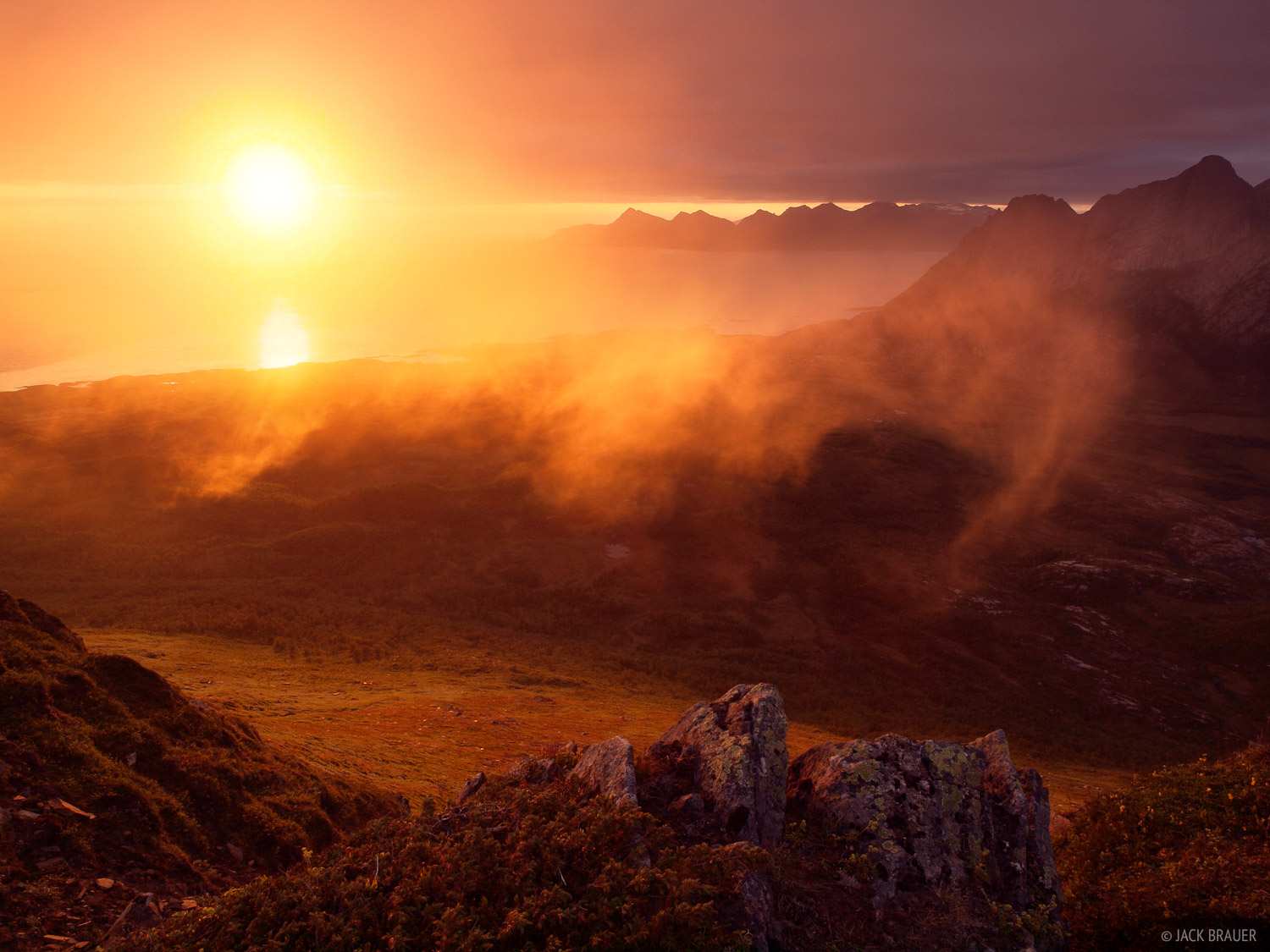 At the end of a dreary overcast day the sun shines a fiery sunset through a gap under the clouds. The famous Strandatindan...