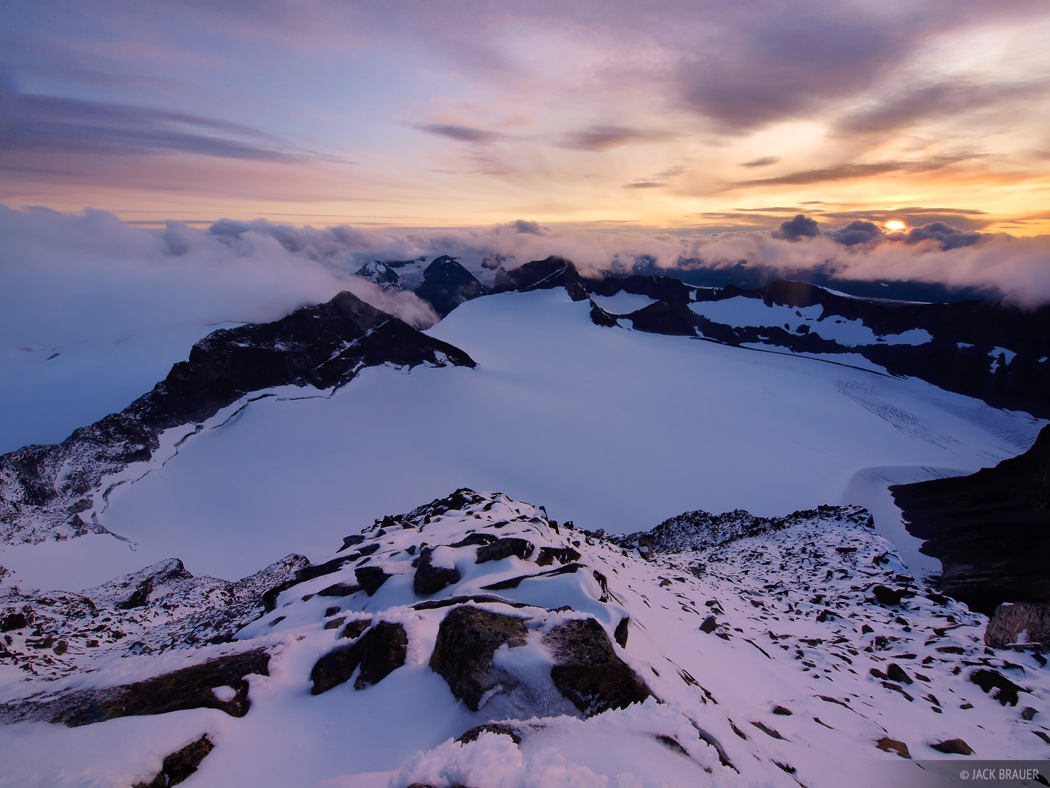 Storm clouds lifted just in time for me to capture this dramatic sunset on the snowy summit of Galdhøpiggen, the tallest...
