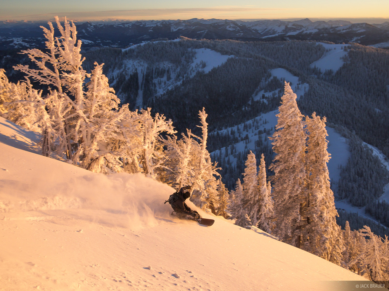 Jason King carves the powder on Teton Pass during beautiful sunset light - January.