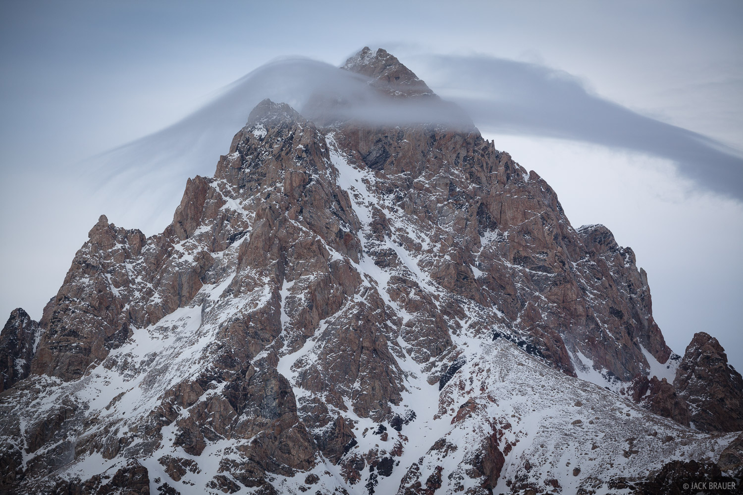 A streamer cloud hovering over the Grand Teton warns of a windy night - March.