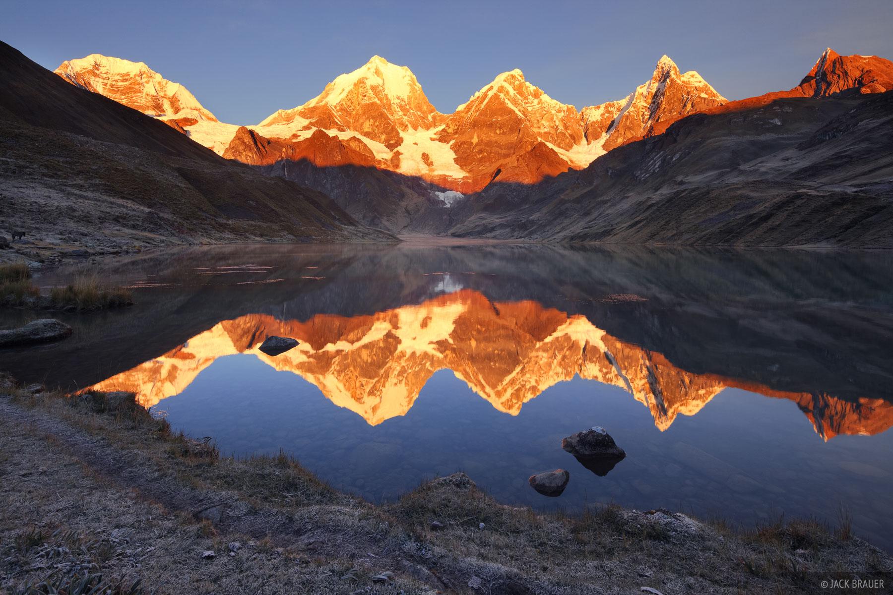 Brilliant sunrise alpenglow on the tallest peaks of the Cordillera Huayhuash (Yerupaja, Yerupaja Chico, and Jirishanca), reflected...