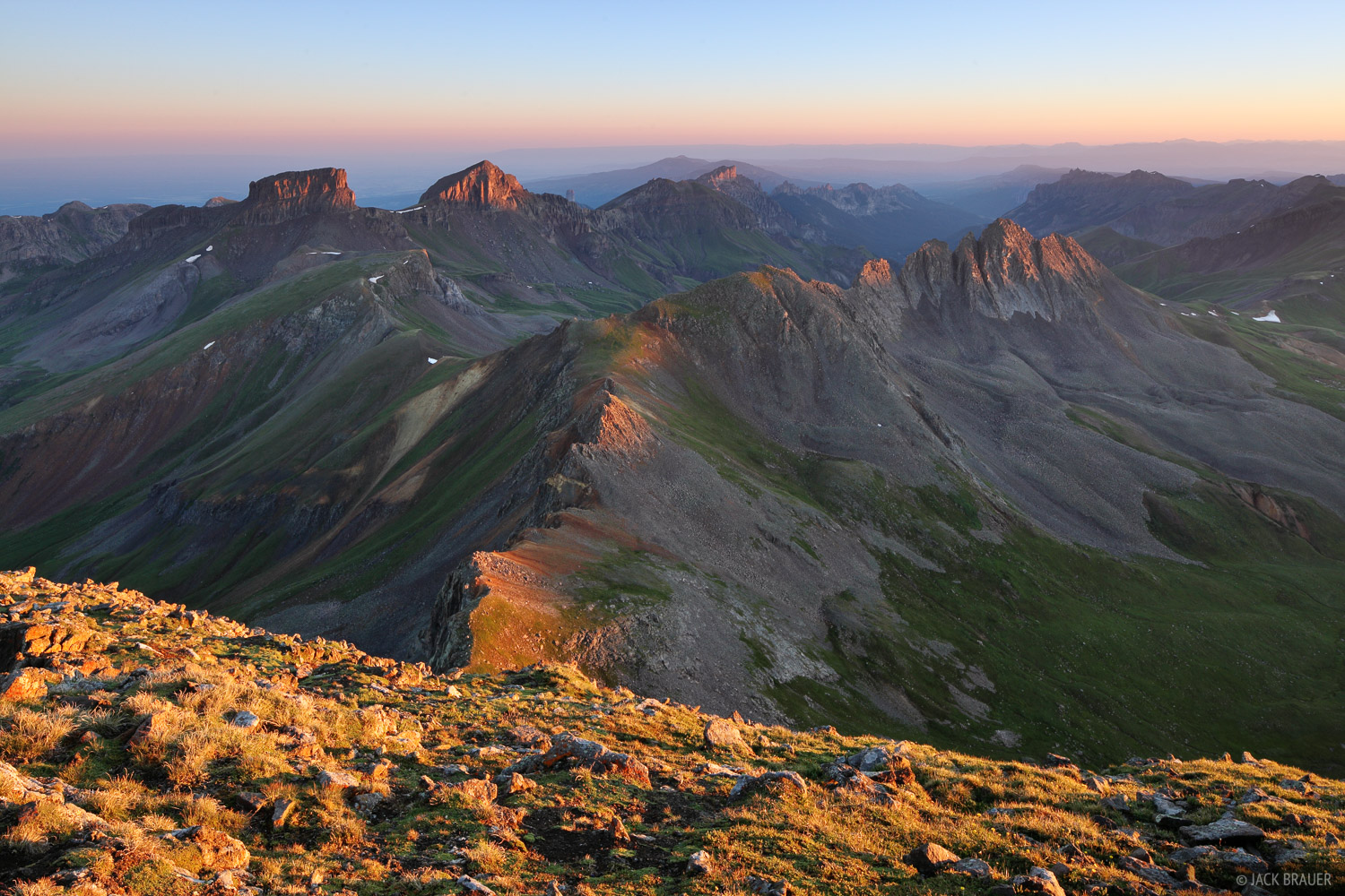 Sunrise alpenglow illuminates the peaks of the Cimarron Range, as seen from the summit of Wetterhorn Peak, 14,015 ft.  ...