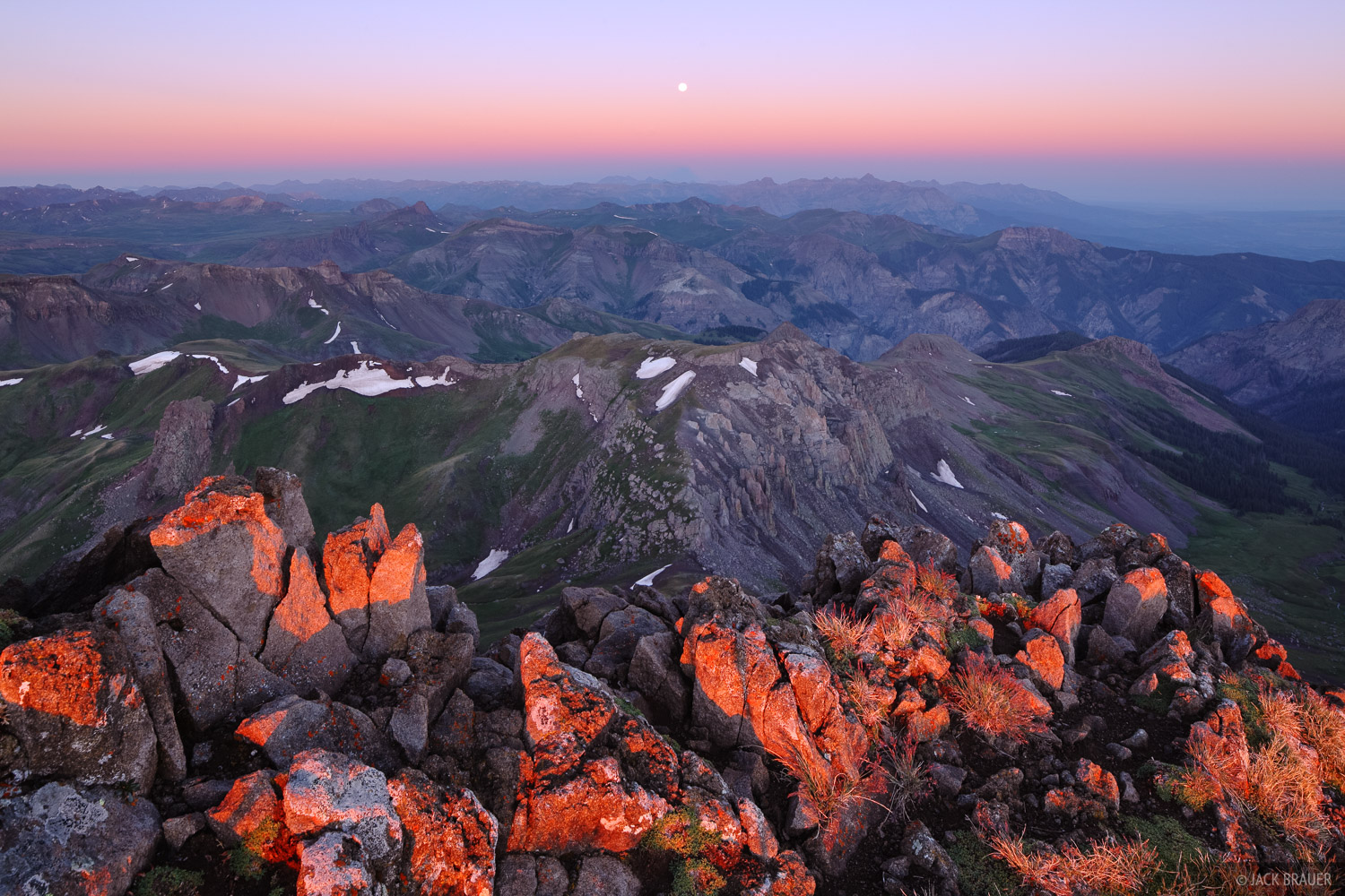 Sunrise over the San Juans, as seen from the summit of Wetterhorn Peak.  At 14,015 ft. the summit rocks of Wetterhorn are...