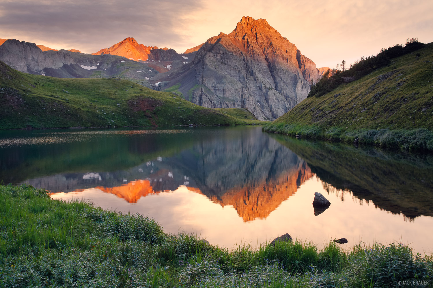Sunrise alpenglow reflection of a rugged peak in the Sneffels Range, as seen from the middle Blue Lake.