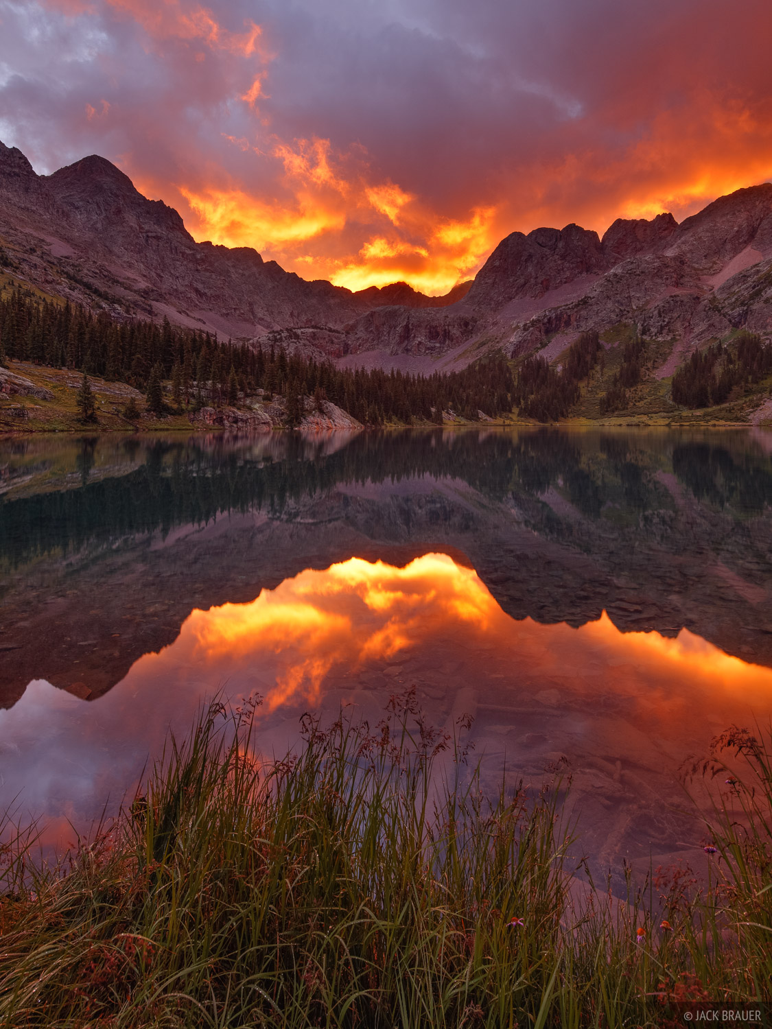 A fiery sunrise relfected in a remote lake near the Grenadier Range, deep in the mountains of the Weminuche Wilderness.