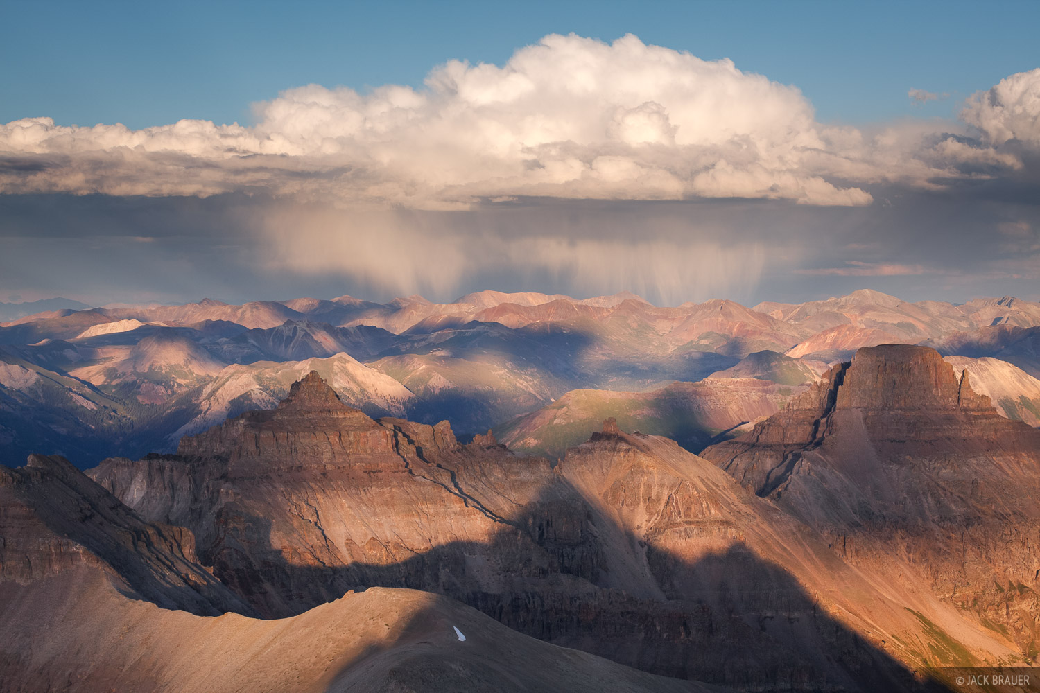 A distant summer shower over the Uncompahgre Wilderness, as seen from the summit of Mt. Sneffels (note the summit shadow in the...