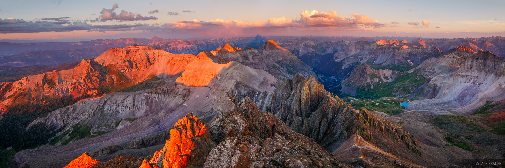 Panoramic view of sunset alpenglow lighting the San Juan Mountains, as seen from the 14,150ft. summit of Mt. Sneffels. ...
