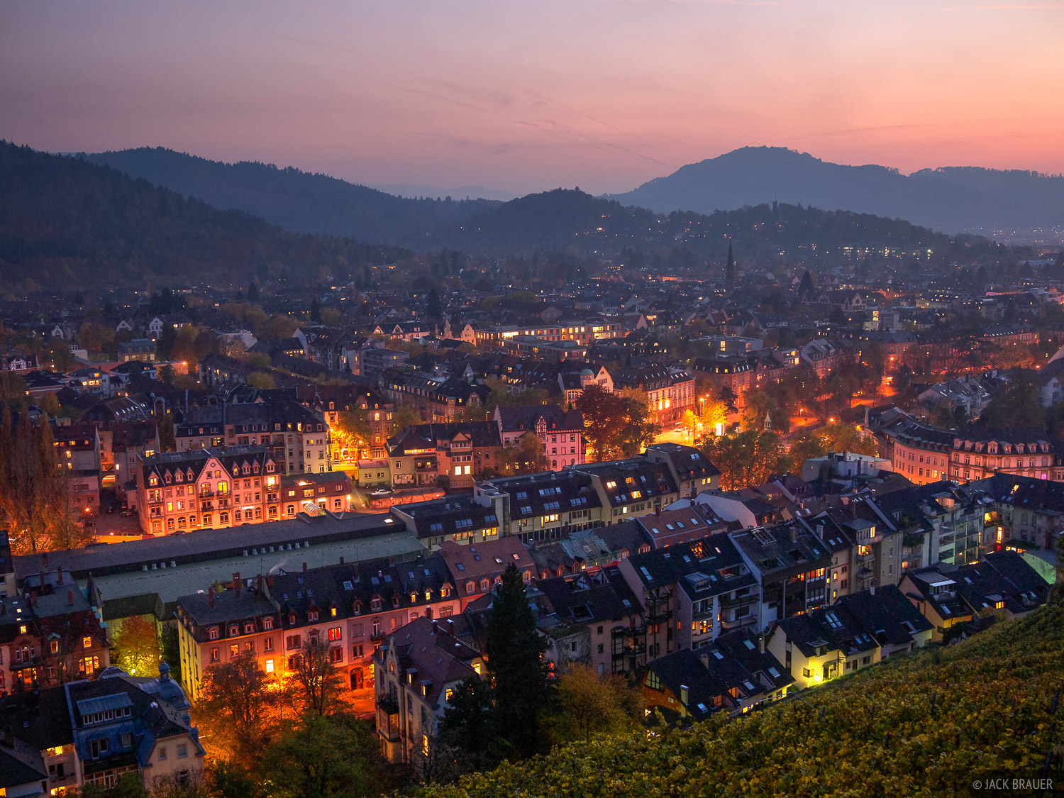 Pink dusk light over the city lights of Freiburg, Germany.