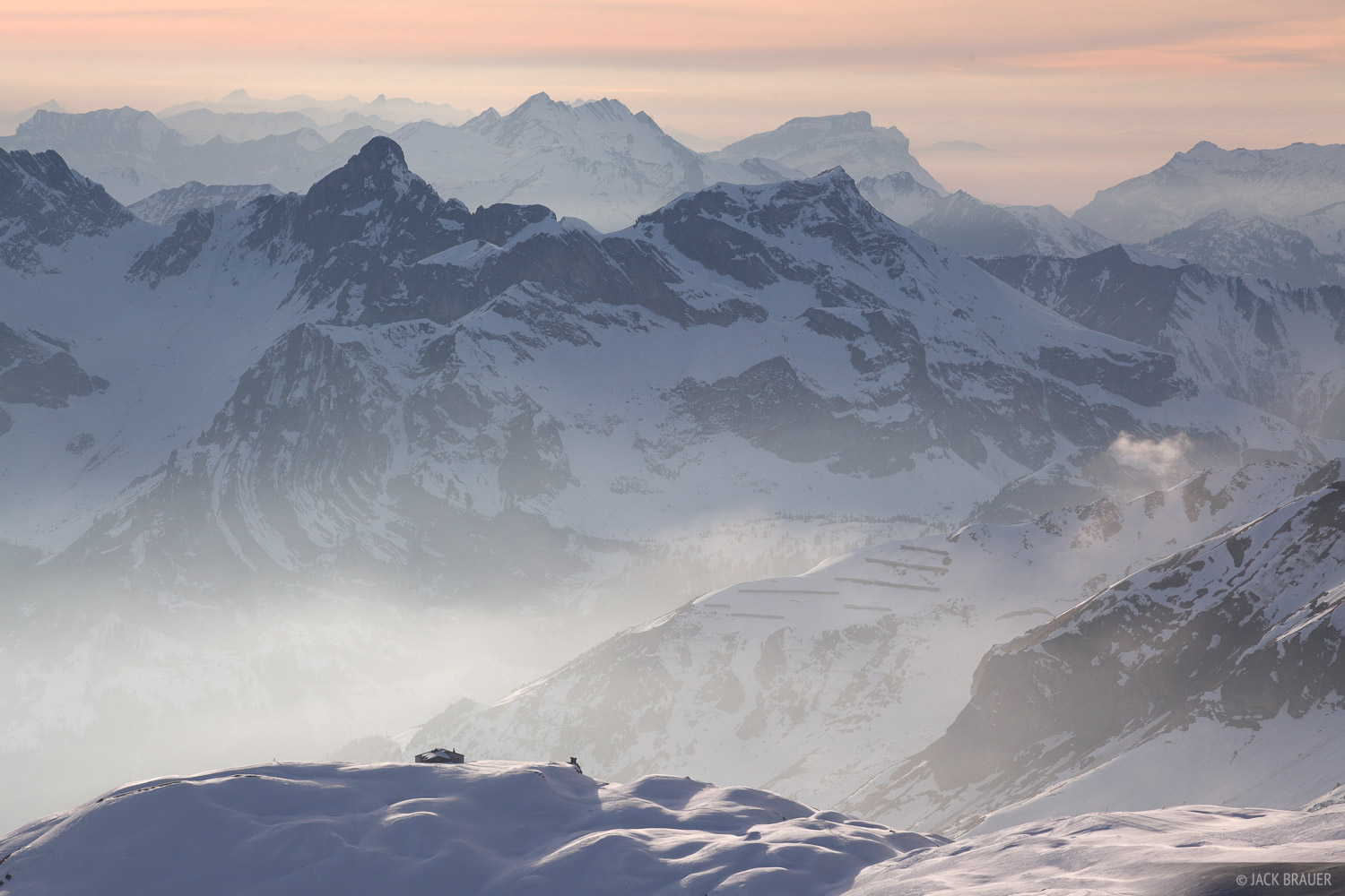 The Rugghubelhüttealpine hut sits on a snowy ridge above Engelberg, with a hazy Swiss Alps backdrop - February.
