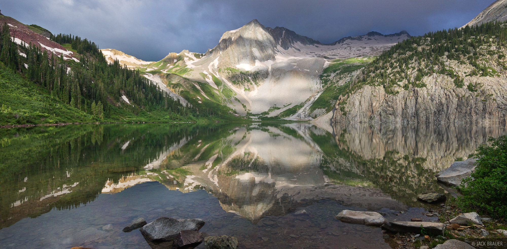 Early morning shadows play on Snowmass Peak, reflected in Snowmass Lake.