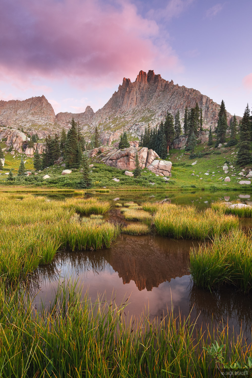 Jagged Mountain reflects in a small pond at sunrise in the Weminuche Wilderness.