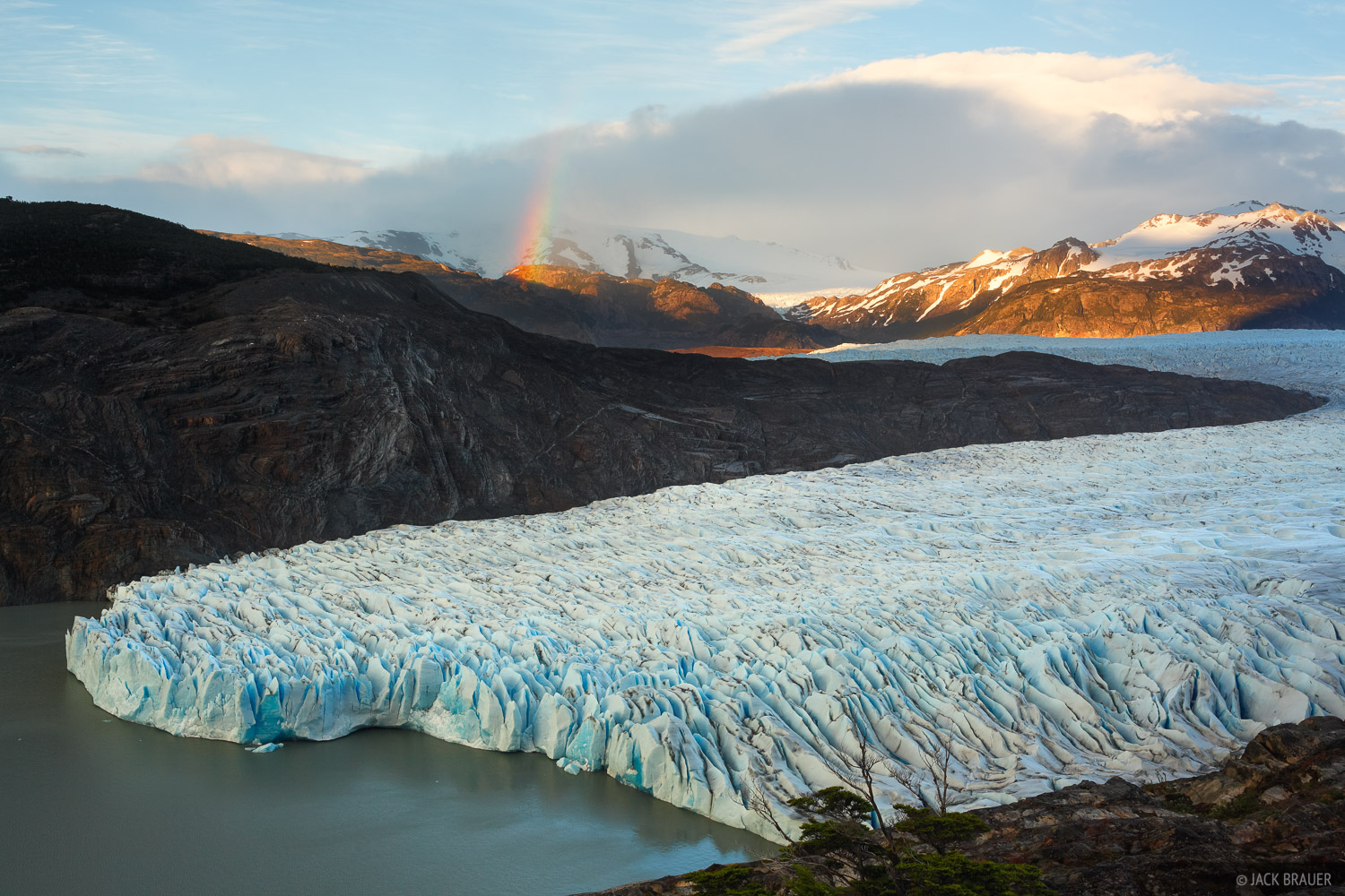 A small rainbow appears above the snout of Glaciar Grey at sunrise.