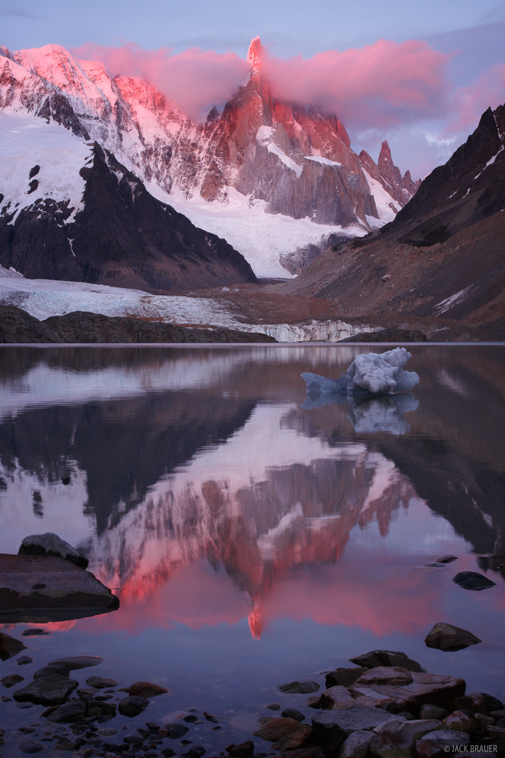 The piercing spire of Cerro Torre reflects in Lago Torre at sunrise - December.
