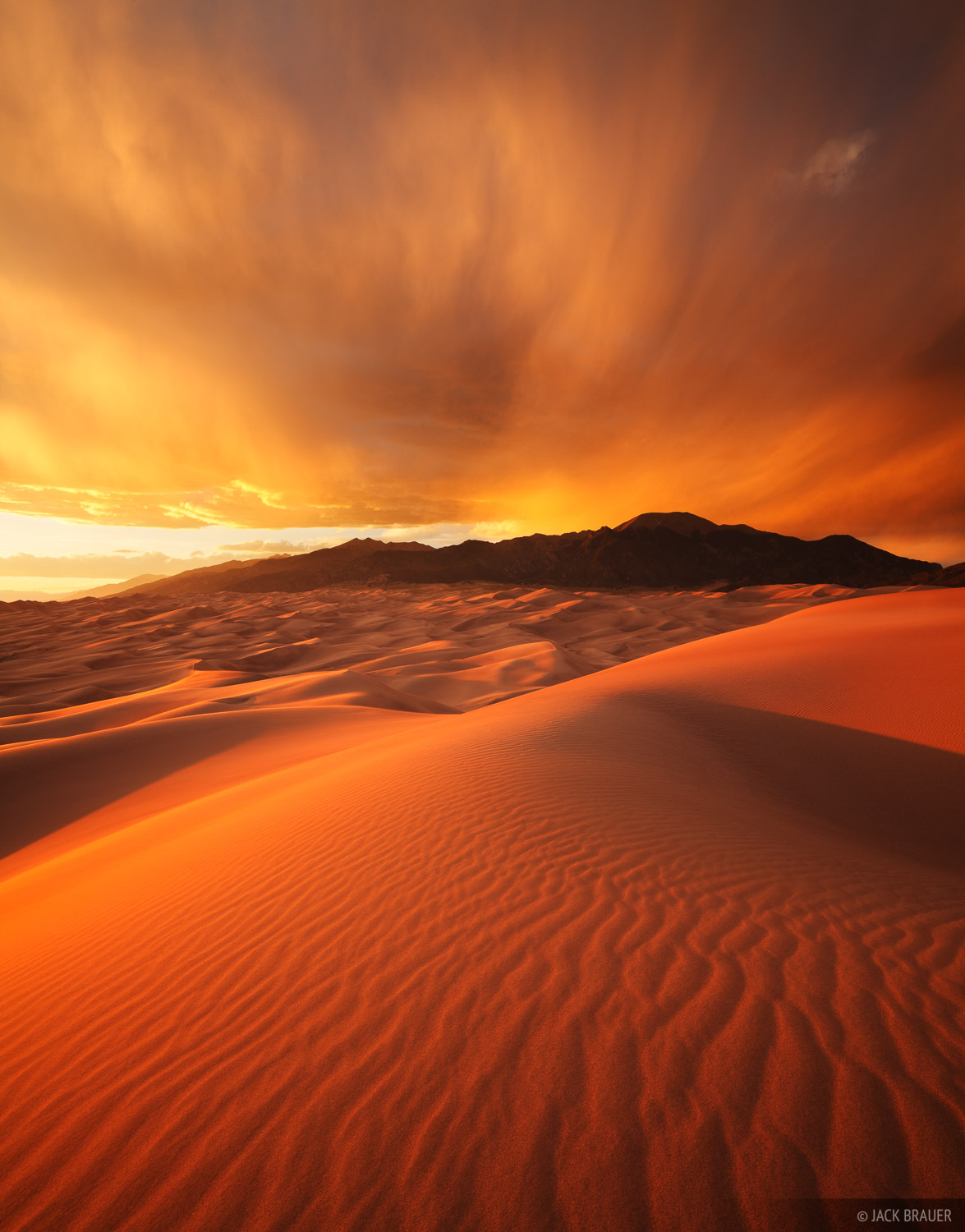 A fiery sunset over the Great Sand Dunes with the Sangre de Cristo mountains behind - June.