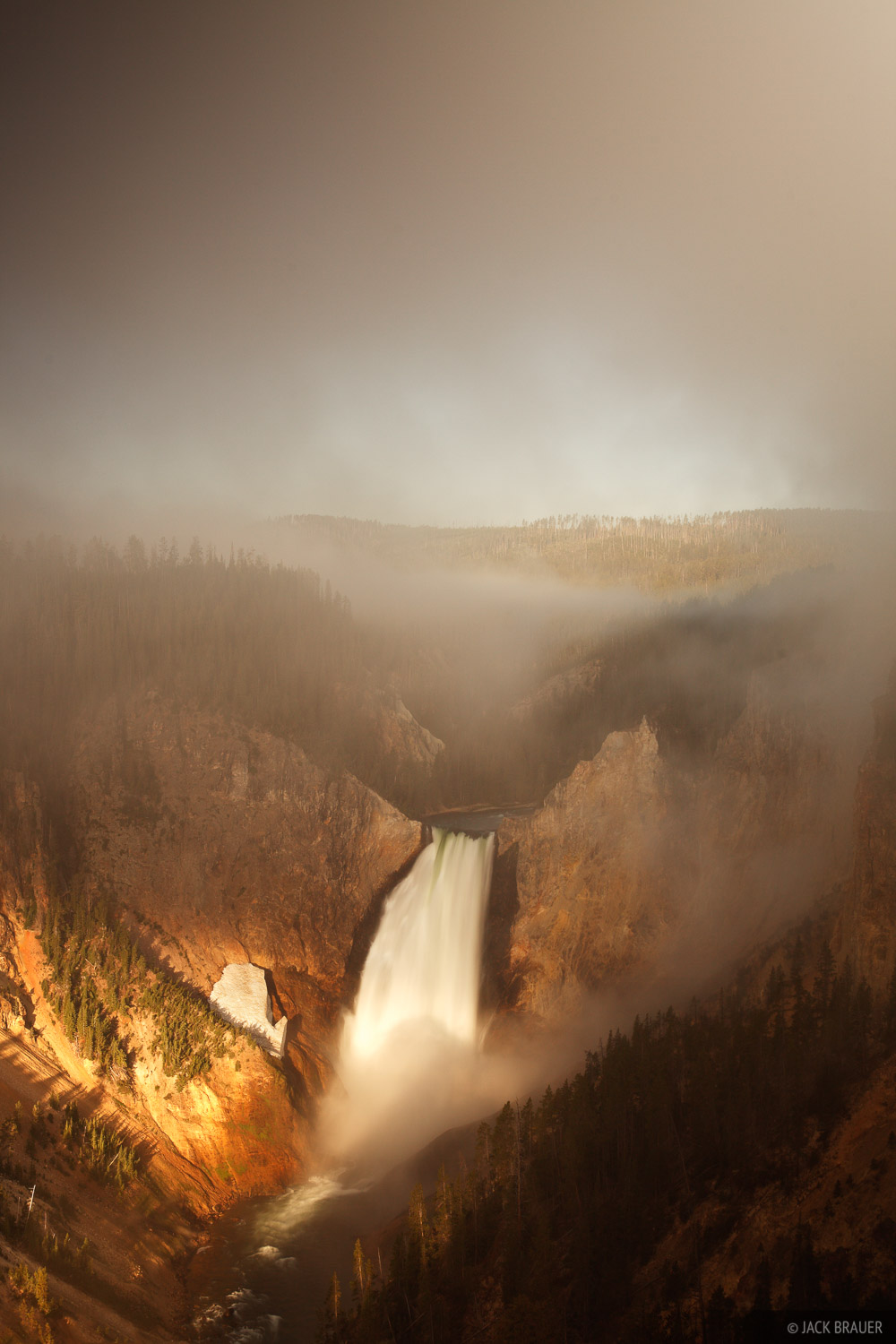 Sunrise light shines on the lower waterfall of the Yellowstone River on a misty morning in the Grand Canyon of the Yellowstone...