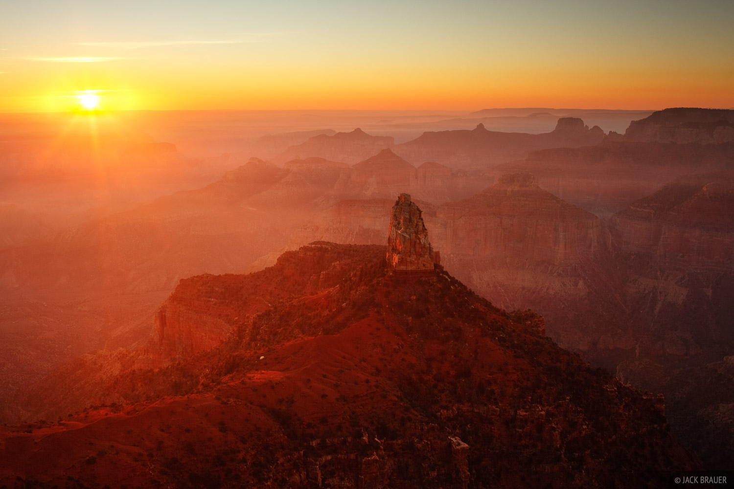 Sunrise light beams through the haze of prescribed wildfire burns along the North Rim of the Grand Canyon, as seen from Point...