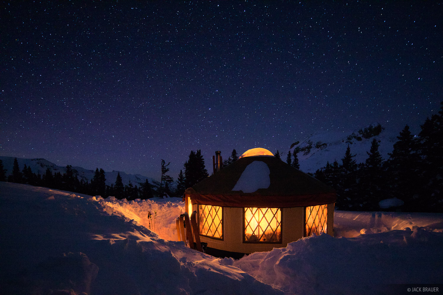 A cozy backcountry yurt in the snow on a winter night in March.