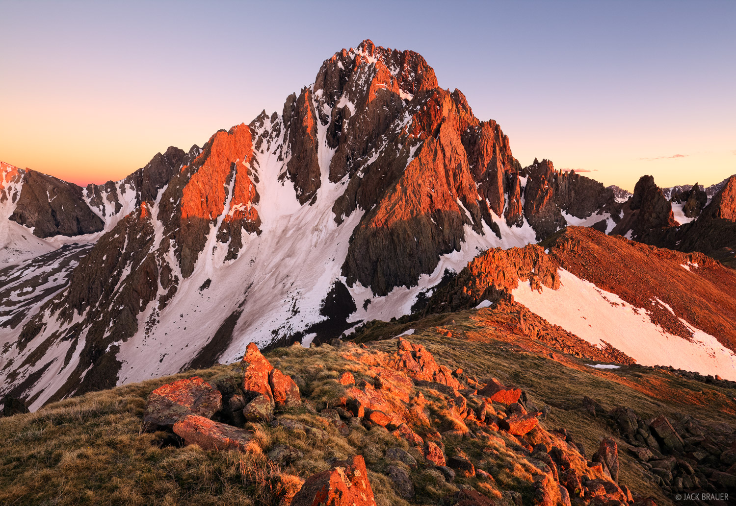 Sunset light illuminates the 14,150 ft. summit of Mt. Sneffels, as seen from a high ridgeline in June, San Juan Mountains.