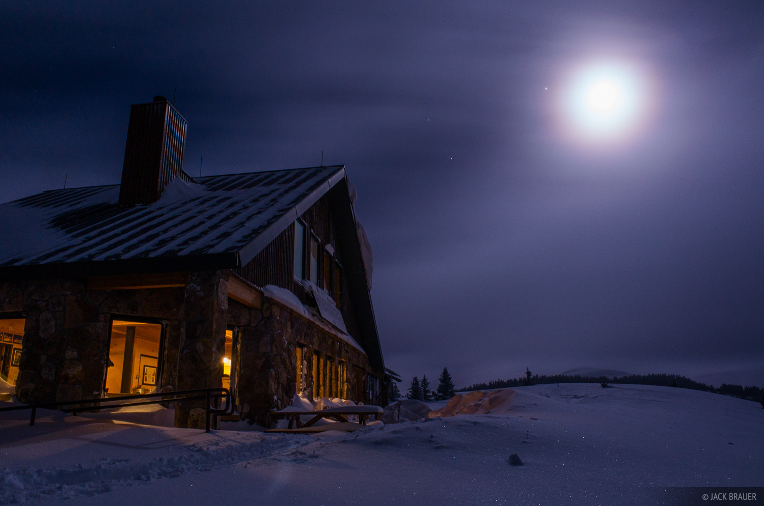 A full moon shines through breaking snowstorm clouds at the Fowler/Hilliard 10th Mountain Division hut - January.