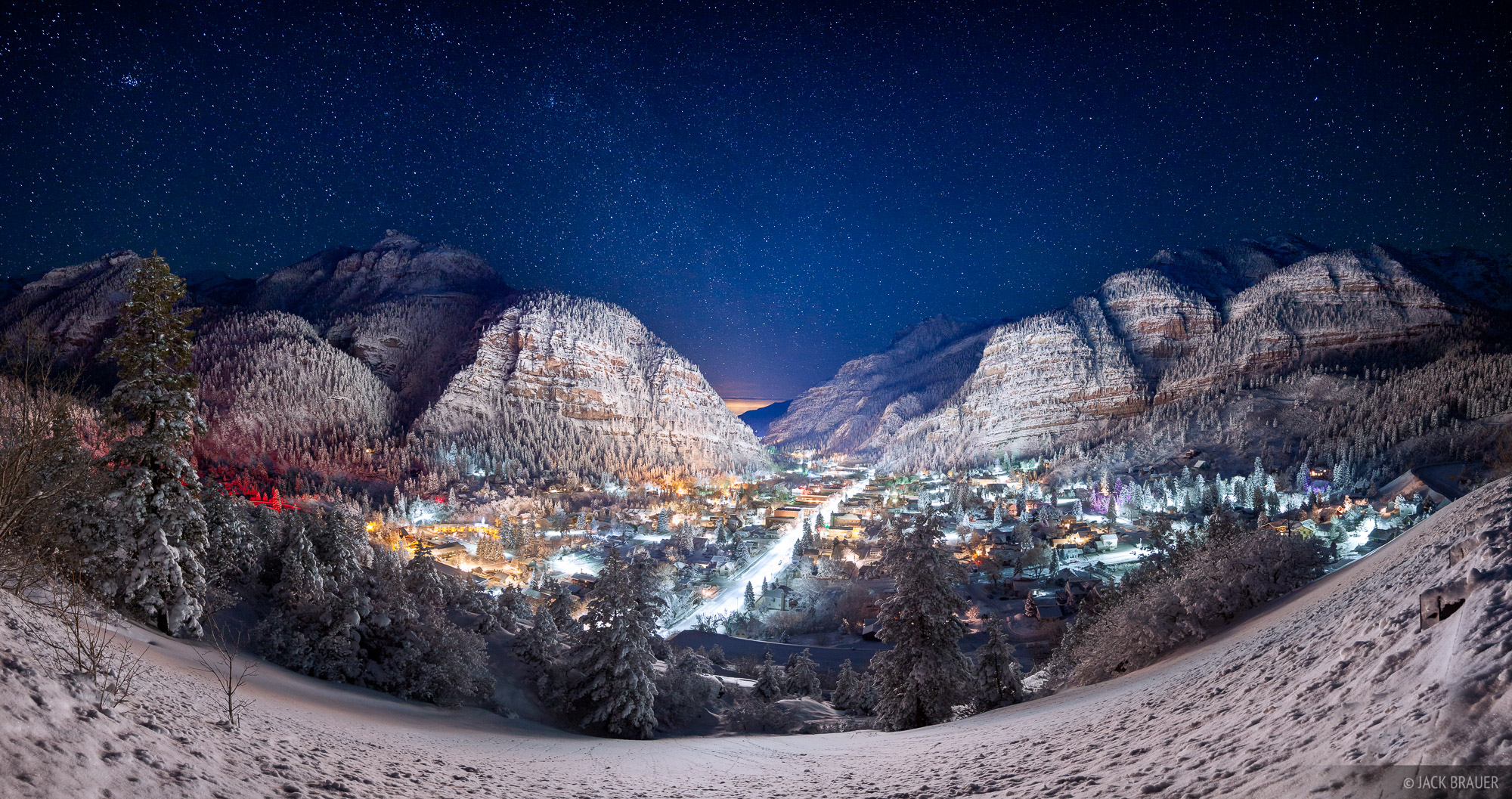 The lights of Ouray, Colorado illuminate the snow-smothered mountains of the Uncompahgre Gorge, as the stars and Milky Way shine...