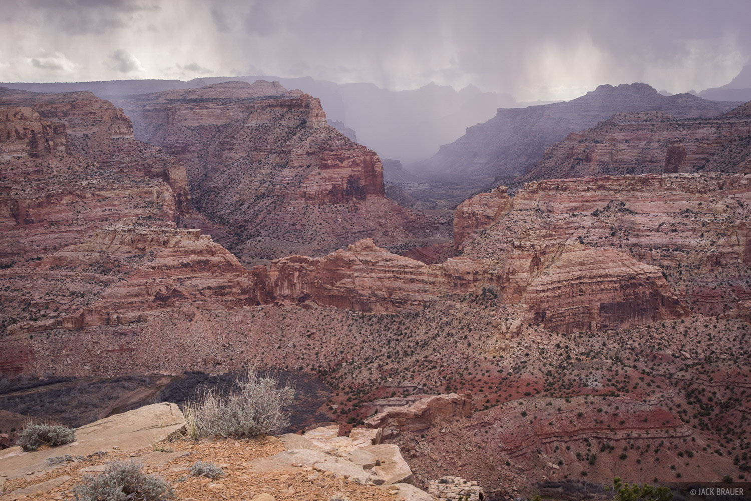 A spring snowstorm passes over the Little Grand Canyon, through which the San Rafael River flows.