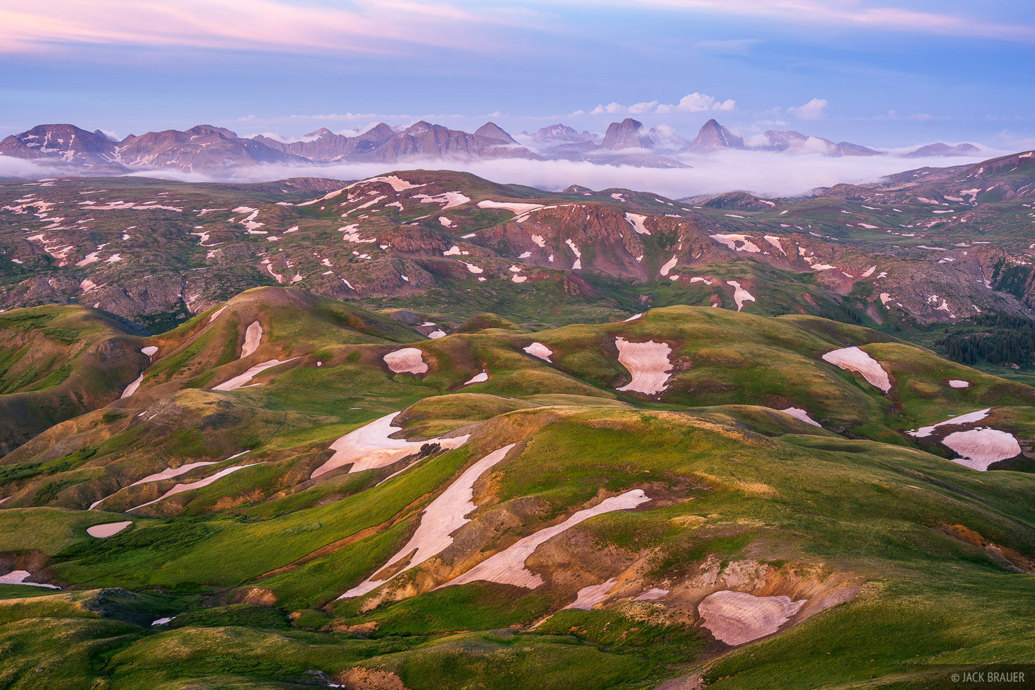 The rugged Grenadier Range rises above the rolling green tundra of the Weminuche Wilderness - July.