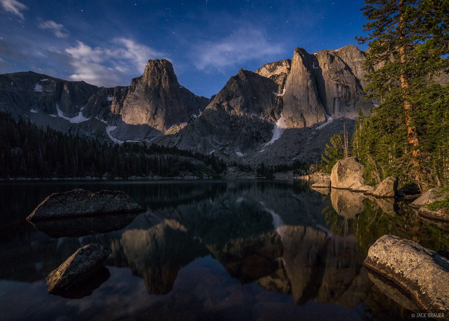 The rising full moon shines on The Monolith and Dogtooth Mountain, reflected in Papoose Lake.