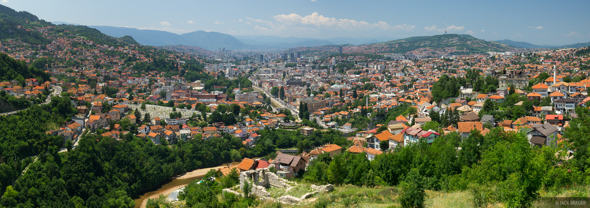 The beautiful city of Sarajevo sits in a verdant valley between rolling hills. Downtown in down in the center.