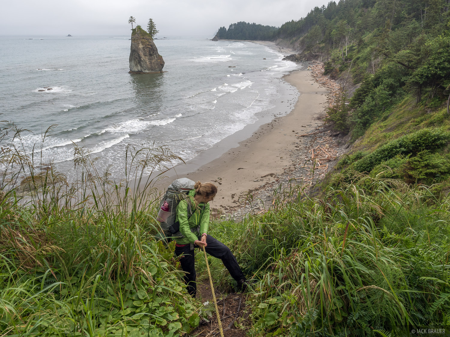 A rope-assisted descent down a steep portion of trail over a rocky headland between beaches.