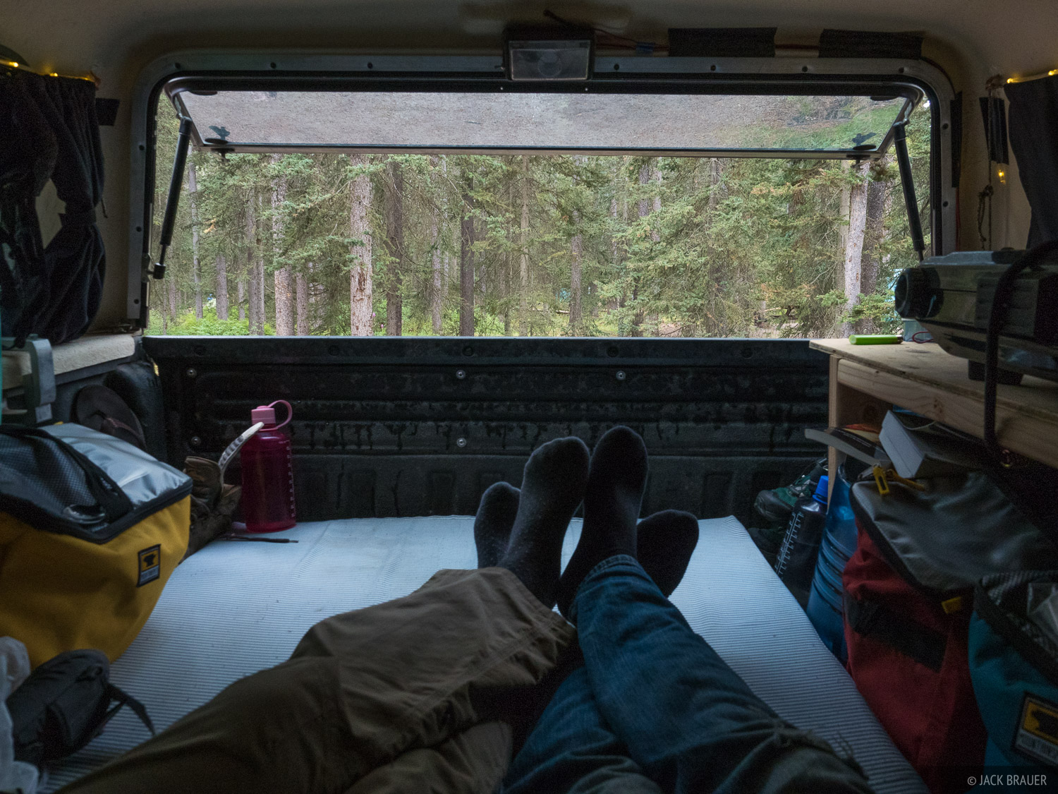Sitting out the rain in the back of the truck at the Lake Louise campground. In this picture you can kind of see our setup back...