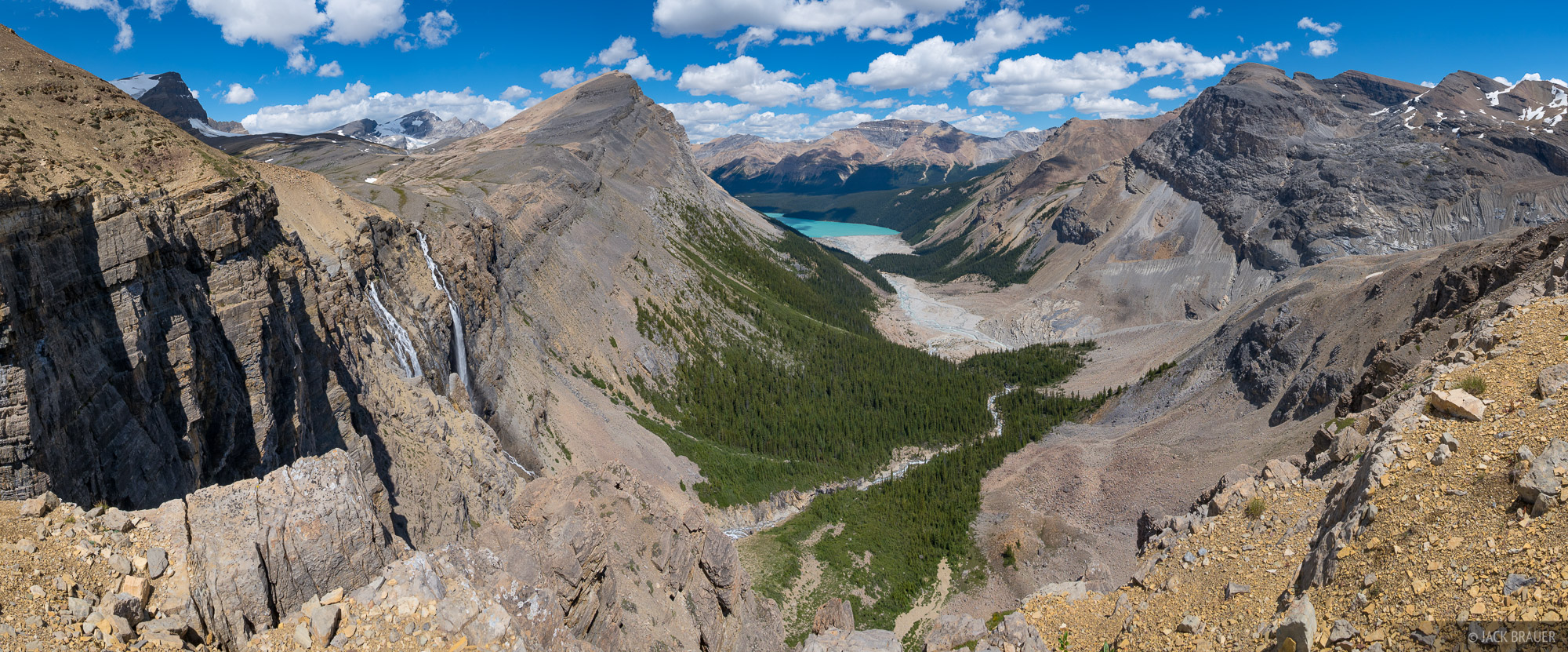 A panoramic view of the waterfall of Cauldron Creek, and the Peyto Creek valley, with Peyto Lake off in the distance.