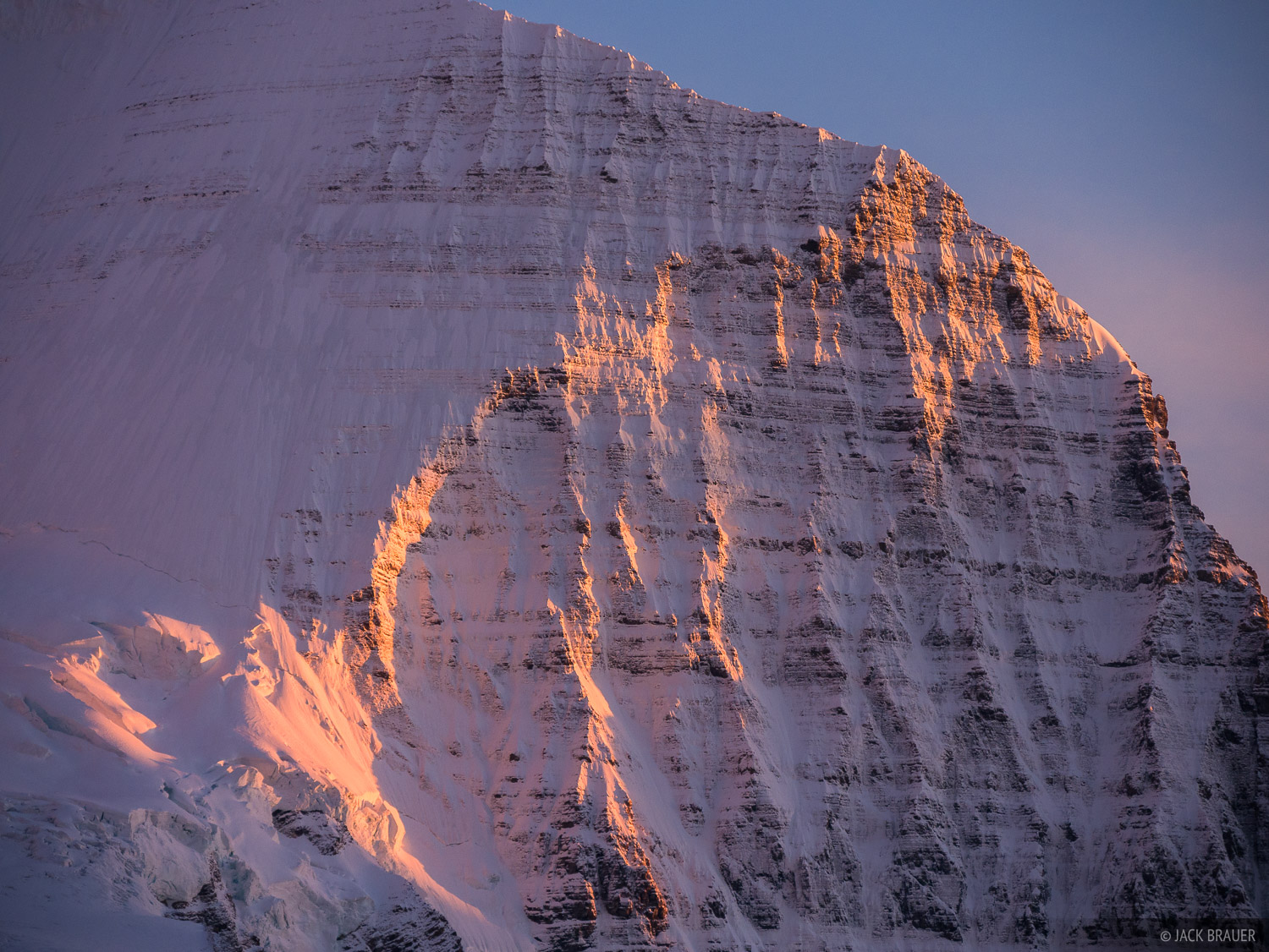 The rugged north face of Mount Robson painted with sunset light.