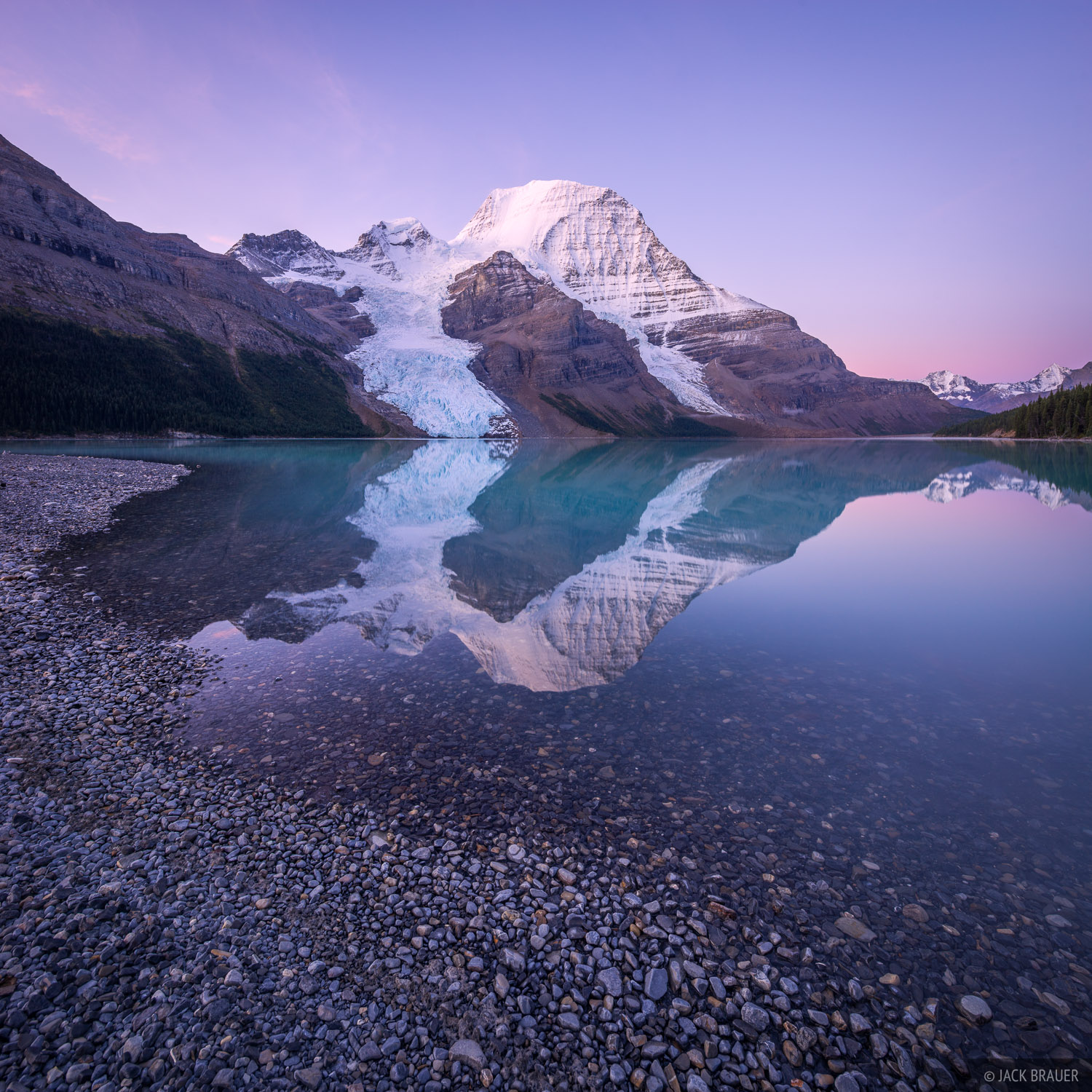 Mount Robson and the Berg Glacier reflect in the calm water of Berg Lake at sunrise.