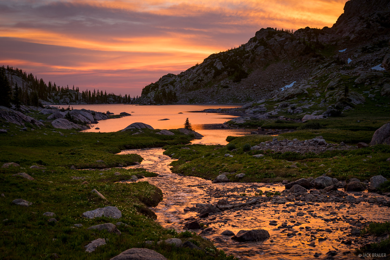 A brilliant sunrise reflects in an alpine stream and lake.